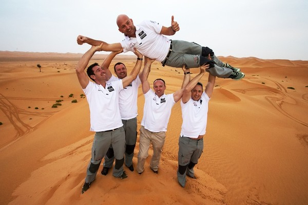 Lo skipper di ADOR Ian Walker sostenuto tra le dune di Abu Dhabi dai nuovi membri del team