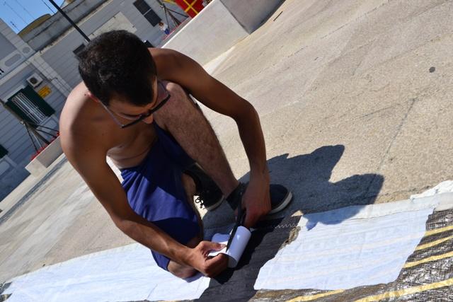 Un membro dell'equipaggio della greca Tazmania Davil è in procinto di riparare il fiocco