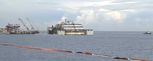La Costa Concordia sollevata di due metri grazie allo svuotamento dei cassoni, mentre viene traianata verso Est dai rimorchiatori