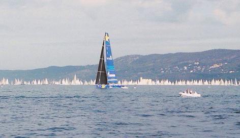 Esimit Europa 2 avanza lentamente verso l'arrivo, sullo sfondo la flotta della Barcolana