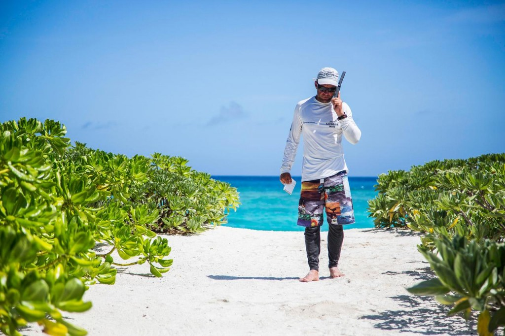 Chris Nicholson al satellitare sulla sabbia bianca dell'atollo. Foto Carlin